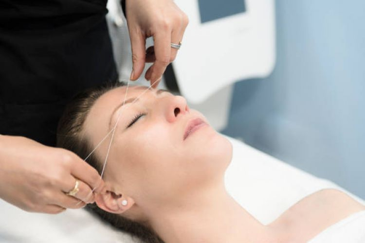woman removing facial hair with Threading
